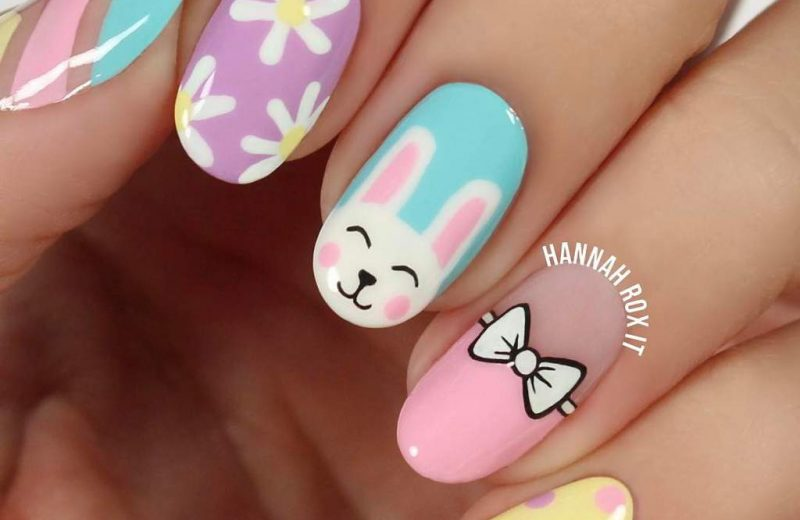 Painted fingernails in various pastel colors and Easter patterns including white daisies, an Easter bunny, a bow, and pastel polka dots.