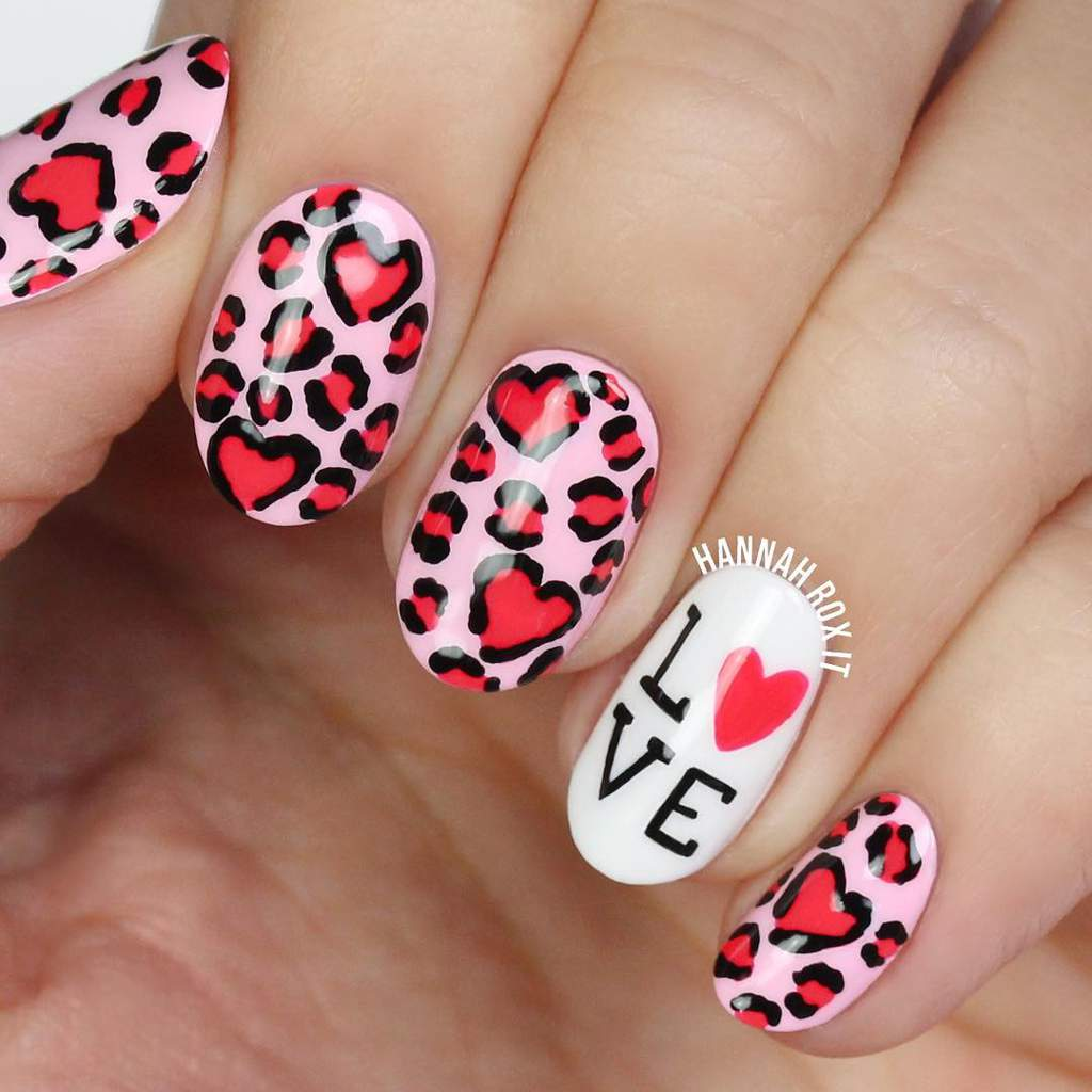 Fingernails with read leopard-print hearts design on a pink background and one with the word Love on a white background with the O replaced with a red heart.