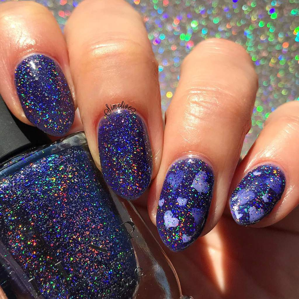 Purple sparkly fingernails, two with pale hearts