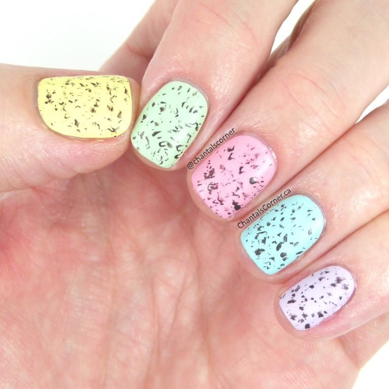 Hand with nails painted in mini-egg speckled design and colors including pale pastel yellow, green, pink, blue and lilac.