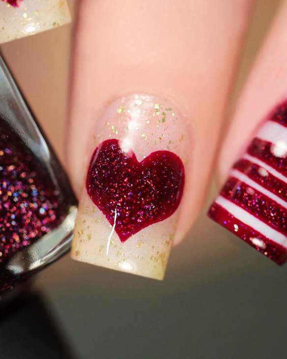 Fingernail with glittery red painted heart design.