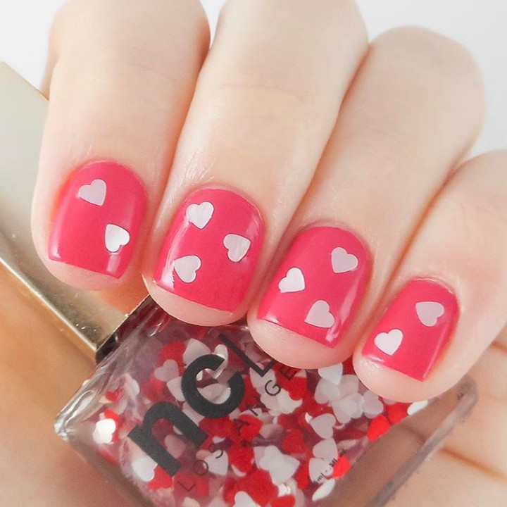 Fingernails with pale hearts embedded on a bright pink background
