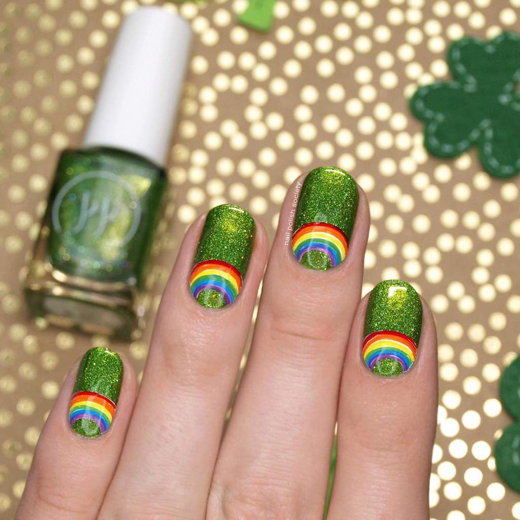 Fingernails with rainbow design on a green glittery background.