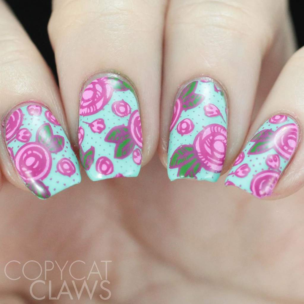 Painted fingernails with pink flowers and green leaves on a pale blue background