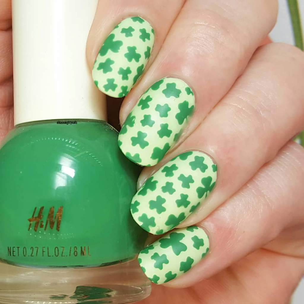 Fingernails with dark green shamrocks on a pale green background.