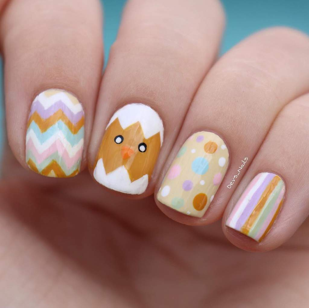 Hand with various Easter themed painted nails. From left to right: Zig-zag stripes, a hatching chick, polka dots and vertical stripes all in pastel Easter colors.