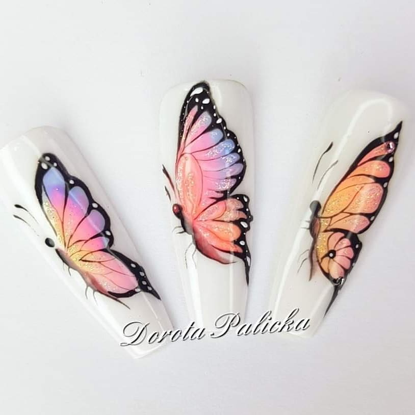 Long white artificial fingernails with beautiful translucent pink, orange and purple butterfly designs.