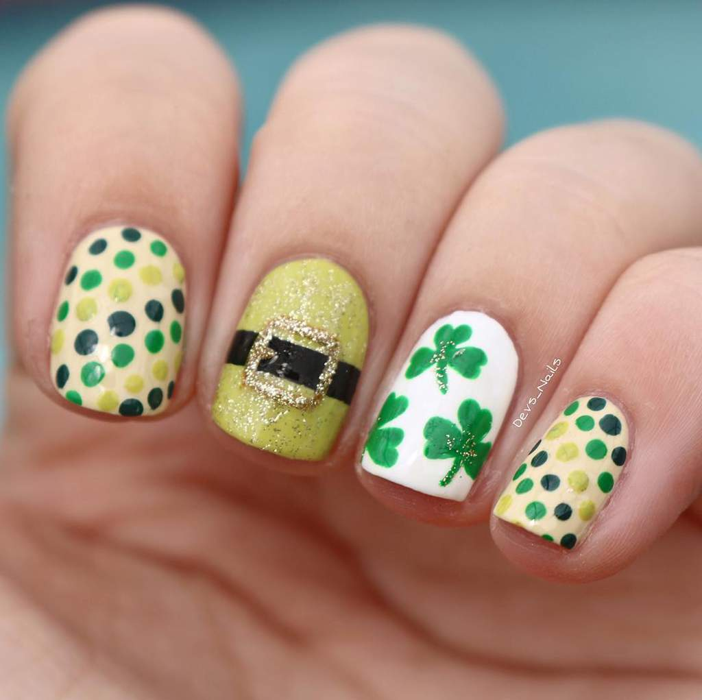 Fingernails with different designs including a leprechaun's hat buckle, green shamrocks and green polka dots.