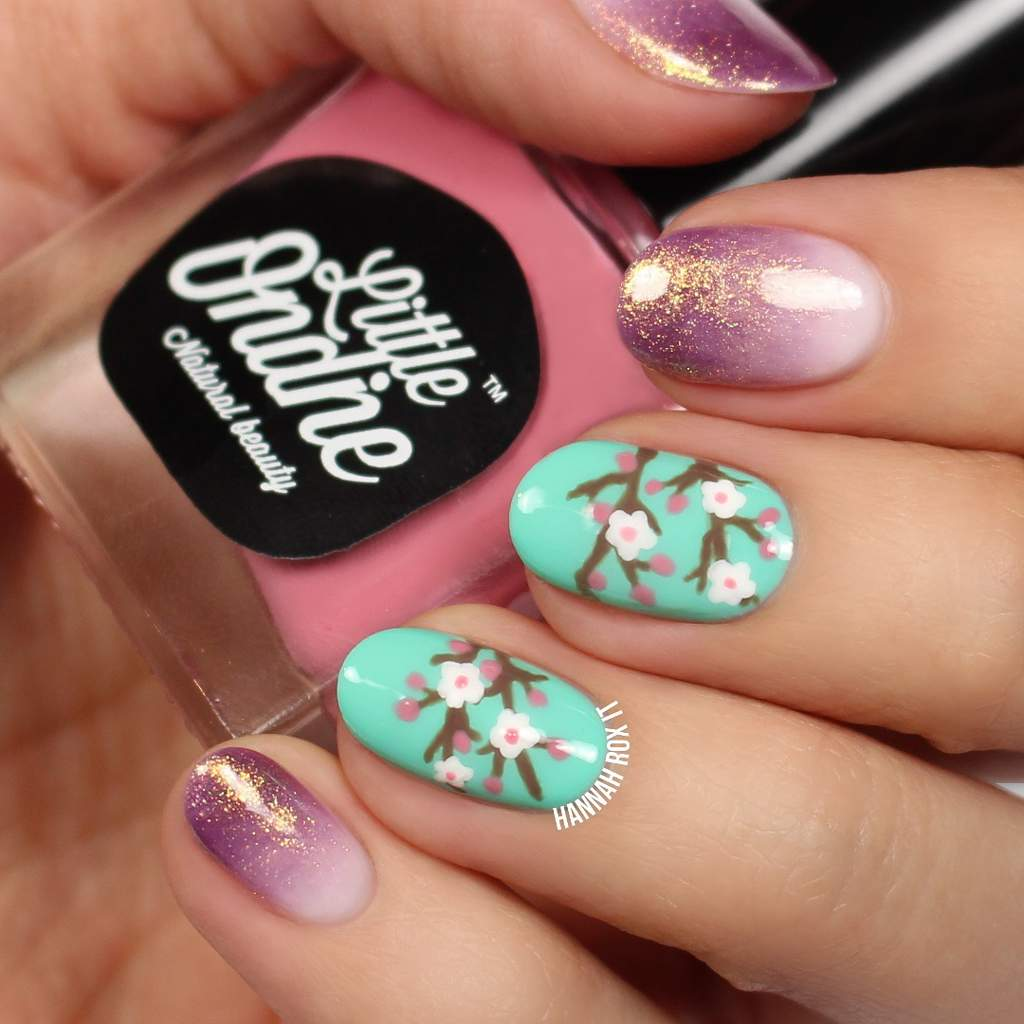 Painted fingernails, 2 with cherry blossom design on aqua colored background and 3 with a white to purple fade and gold glitter.