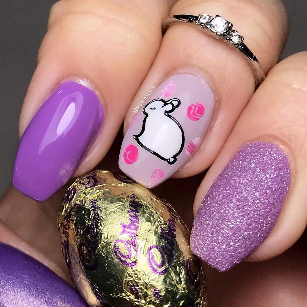 Hand with painted nails holding a foil wrapped chocolate egg. Fingernails are purple gloss, a white bunny surrounded by pink Easter eggs on a pale pink background, and glittery purple.