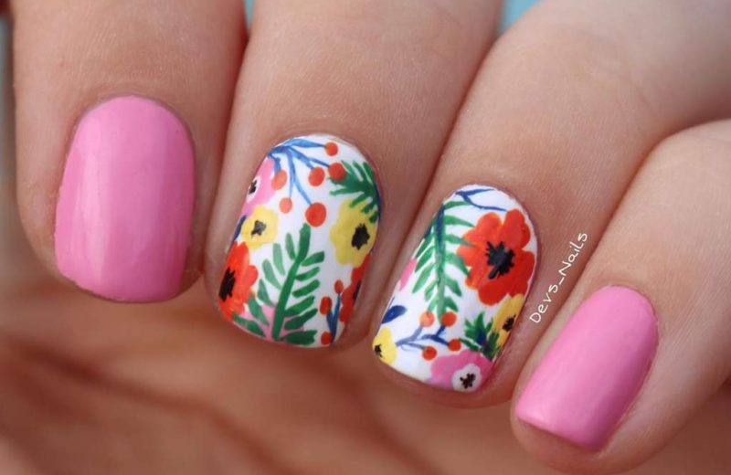 Painted fingernails, two are bright pink and two have painted flower patterns.