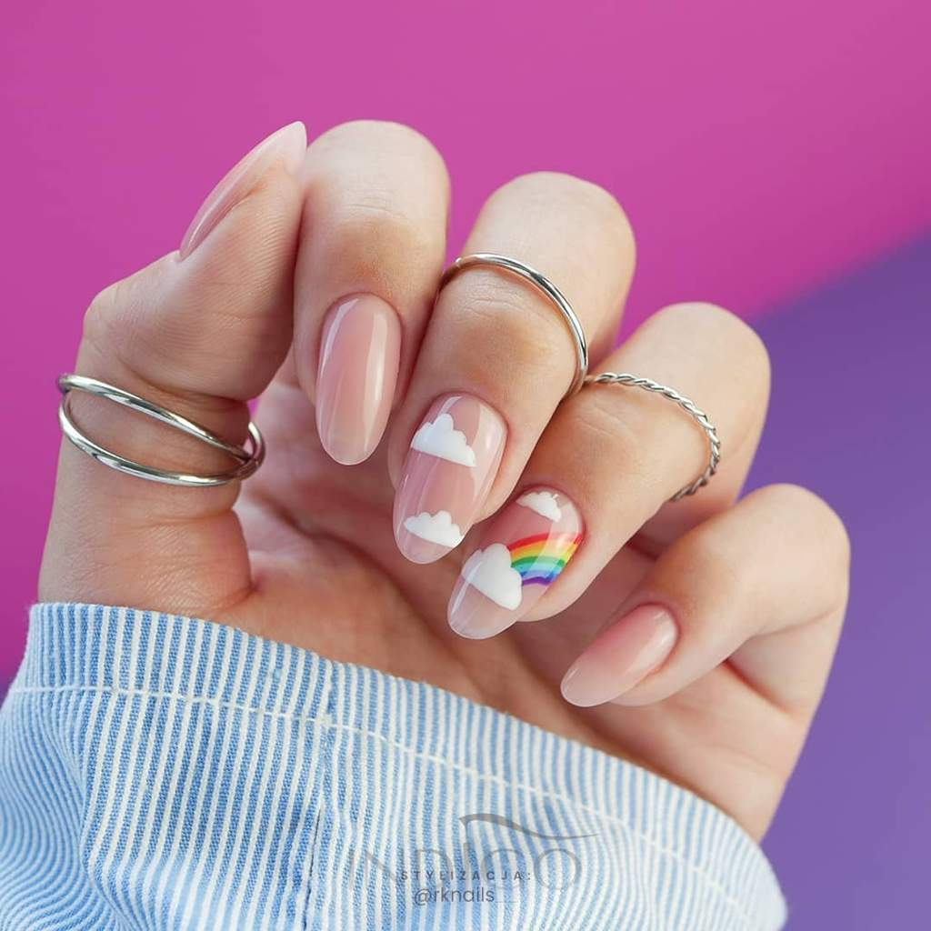Natural colored fingernails, one with white clouds and another with white clouds and a rainbow.