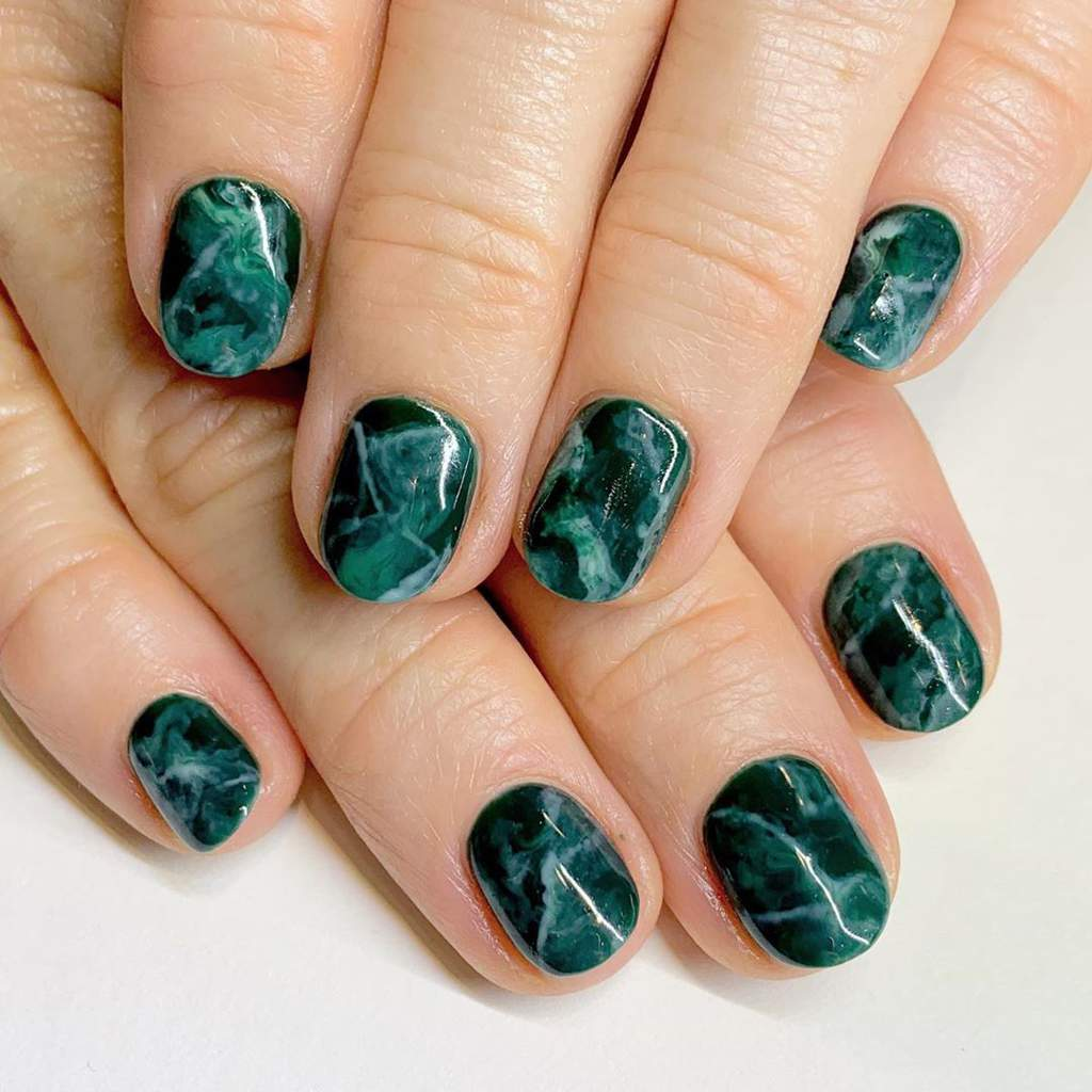 Fingernails with dark green marbled design.