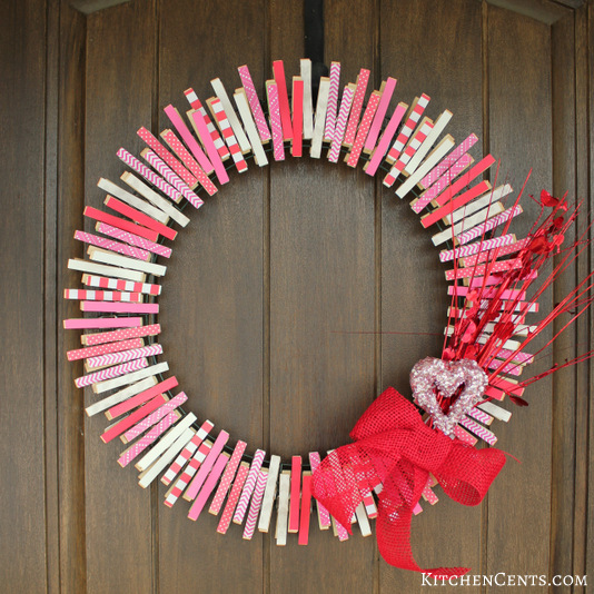 A circular wreath made from mainly pink painted clothespins in different patterns