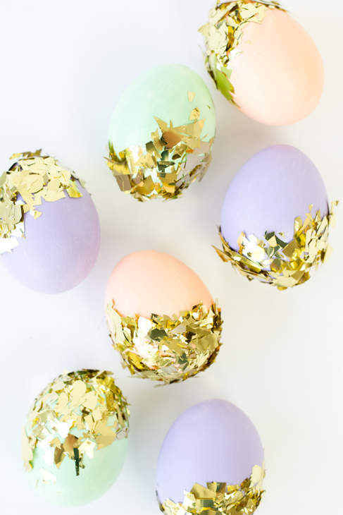 Eggs painted in pale pastel colors in nests of gold foil.