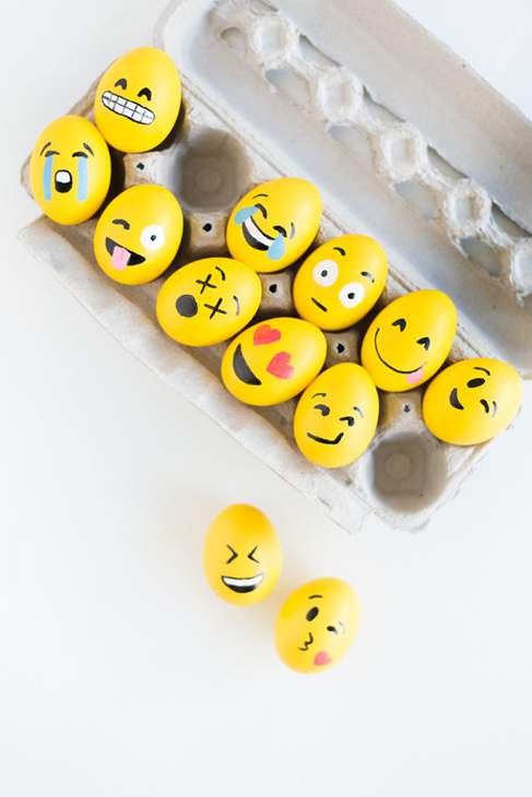10 eggs in an egg-box painted yellow with emoji-style faces with various expressions. There are two loose eggs below the box, painted in the same style.