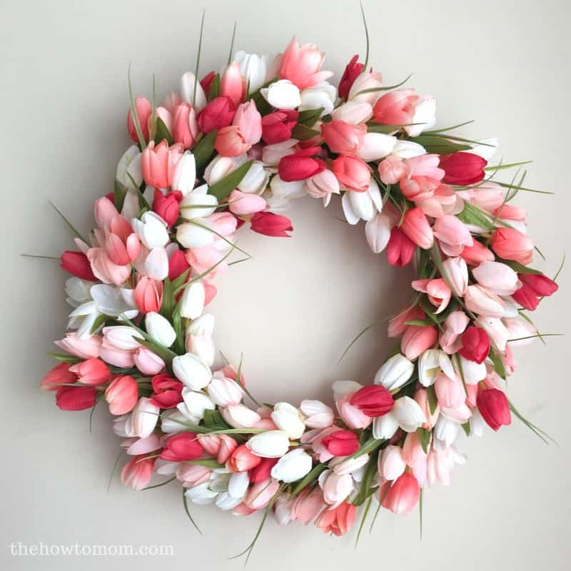 Beautiful wreath of white pink and red tulips with some green foliage.