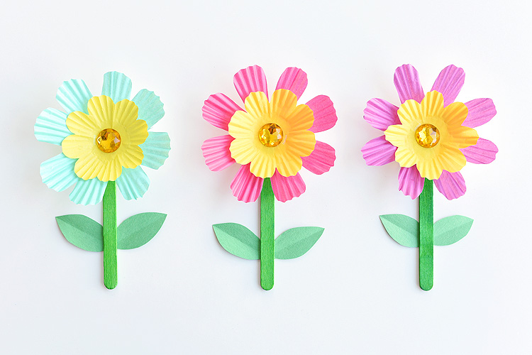 Three brightly colored flowers made from paper.