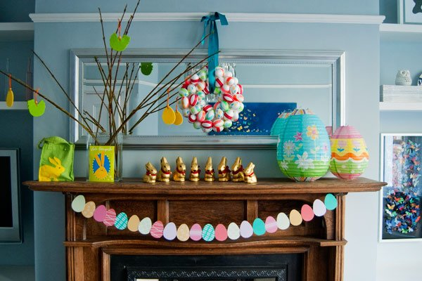 Mantel decorated for Easter with gold chocolate Easter bunnies, large decorated paper egg decorations, a hanging egg-wreath and a banner of paper eggs.