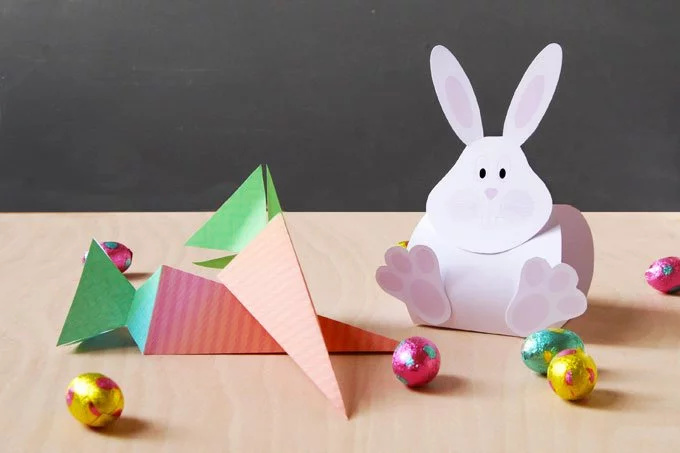 A 3D pink paper rabbit, two triangular paper carrots and some foil-wrapped chocolate Easter eggs sitting on a table.