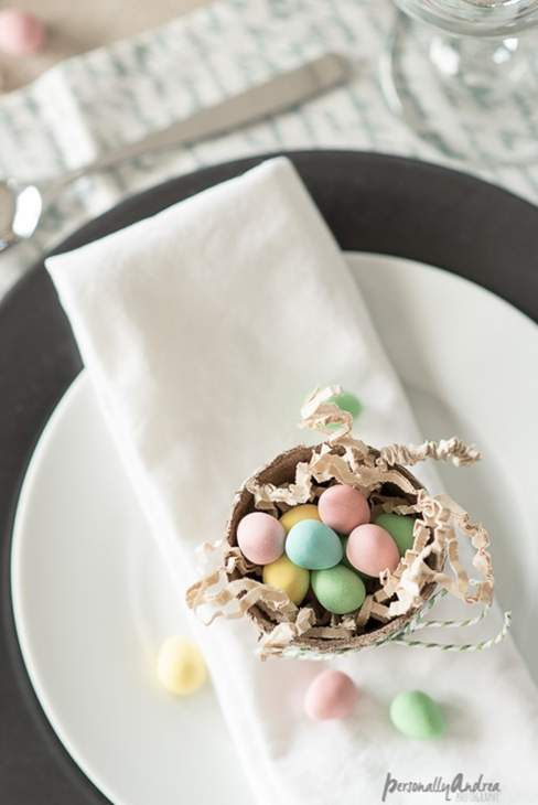 Place setting with pot of mini Easter eggs on a napkin sitting on a plate