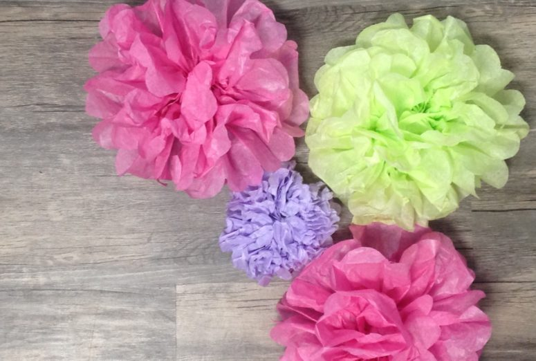 Four tissue paper flowers, two pink, on purple and one light green