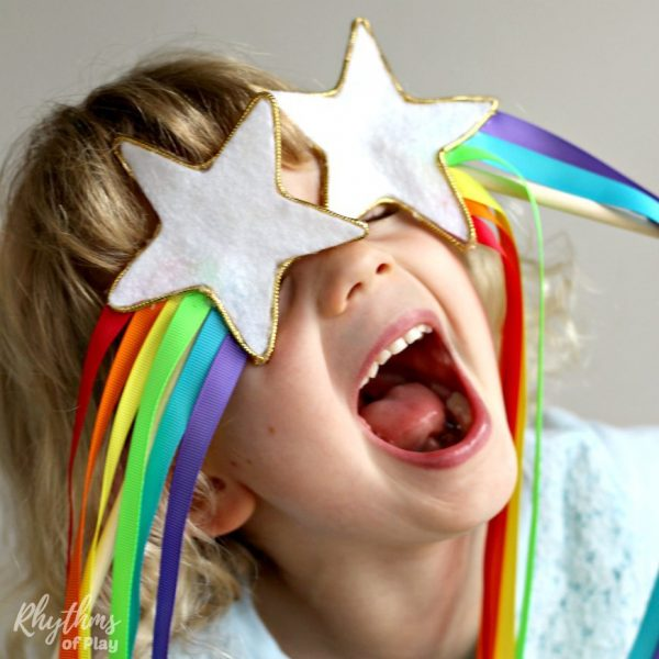 Young girl laughing with a white star over each eye with rainbow-colored ribbons coming from each star