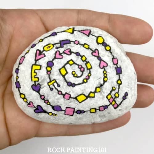 A white rock painted with a message in yellow and pink spiral pattern.