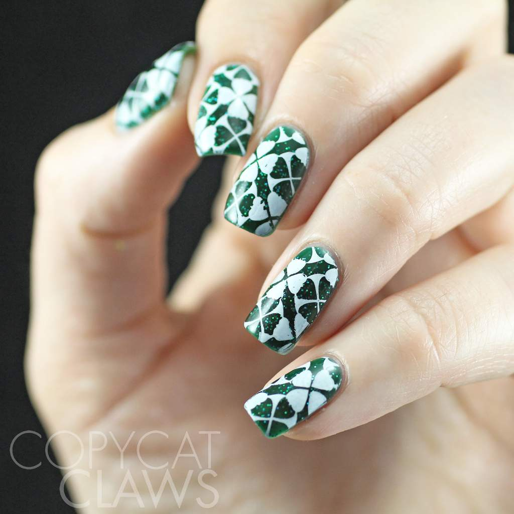 Fingernails with white shamrocks design on a dark green glittery background.