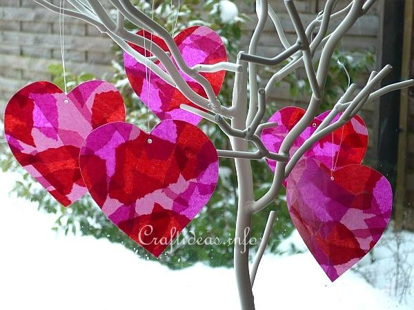 5 paper hearts in pink and red, hanging from a twig in front of a window with snow outside.