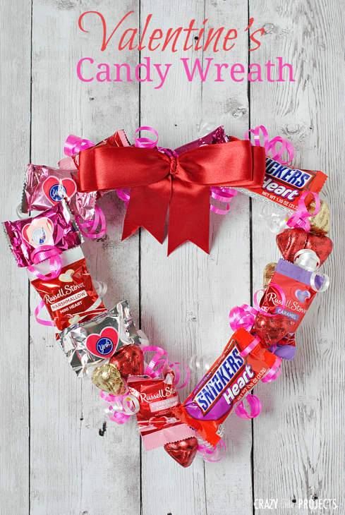 A heart-shaped wreath made from different sorts of candy tied with a red ribbon bow at the top.
