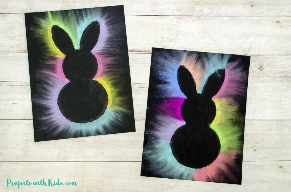 Two rabbit silhouettes outlined with brightly colored pastels.