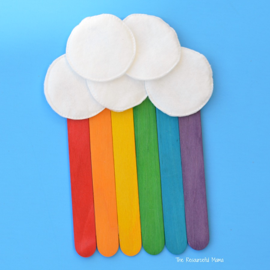 A fluffy white cloud on a sky-blue background with craft sticks painted in rainbow colors coming out of the cloud.