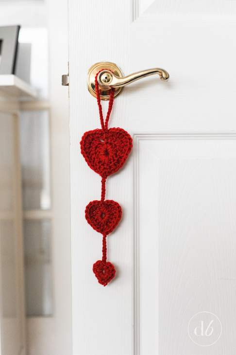 Red crocheted heart door hanger with a large, medium and small woollen heart hanging from a brass door handle on a white door.