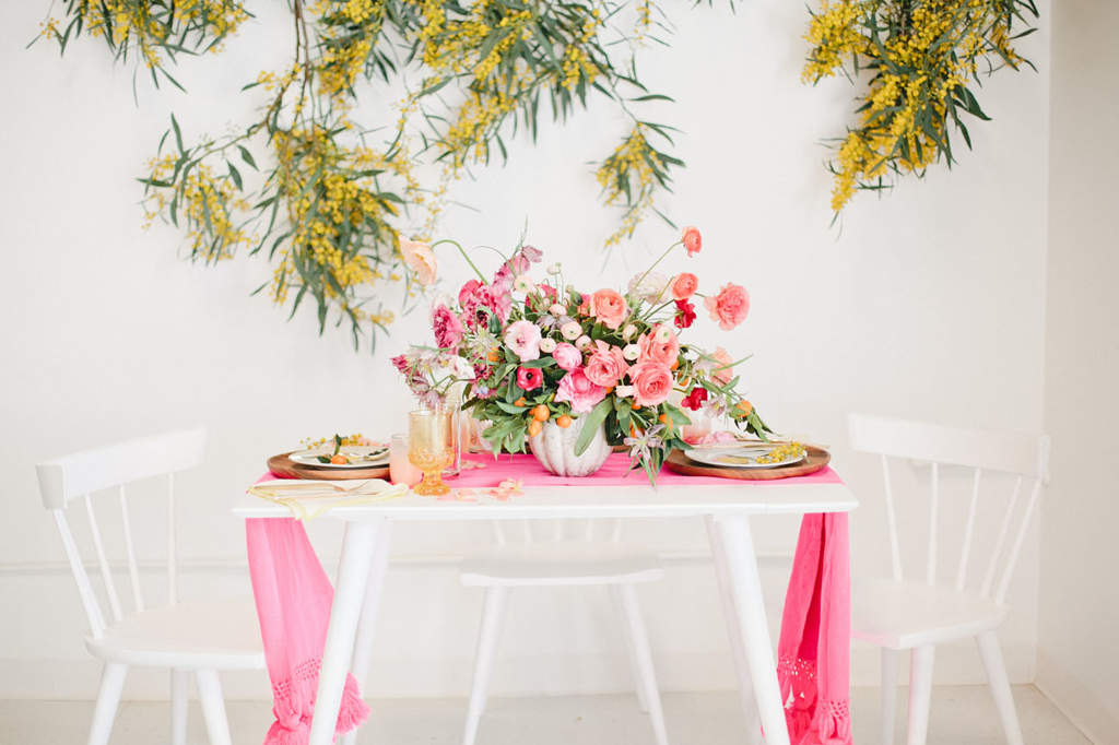 A white table and three chairs with a pink cloth and pink flower arrangement in front of a white wall with a plant with yellow flowers.