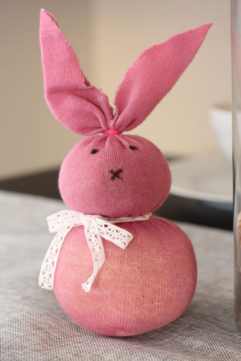 A pink bunny rabbit made from a sock, with a white lacy bow round its neck.