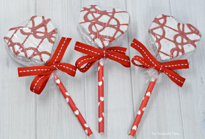 Three white and red heart-shaped treats with red ribbons on red sticks with white heart design.