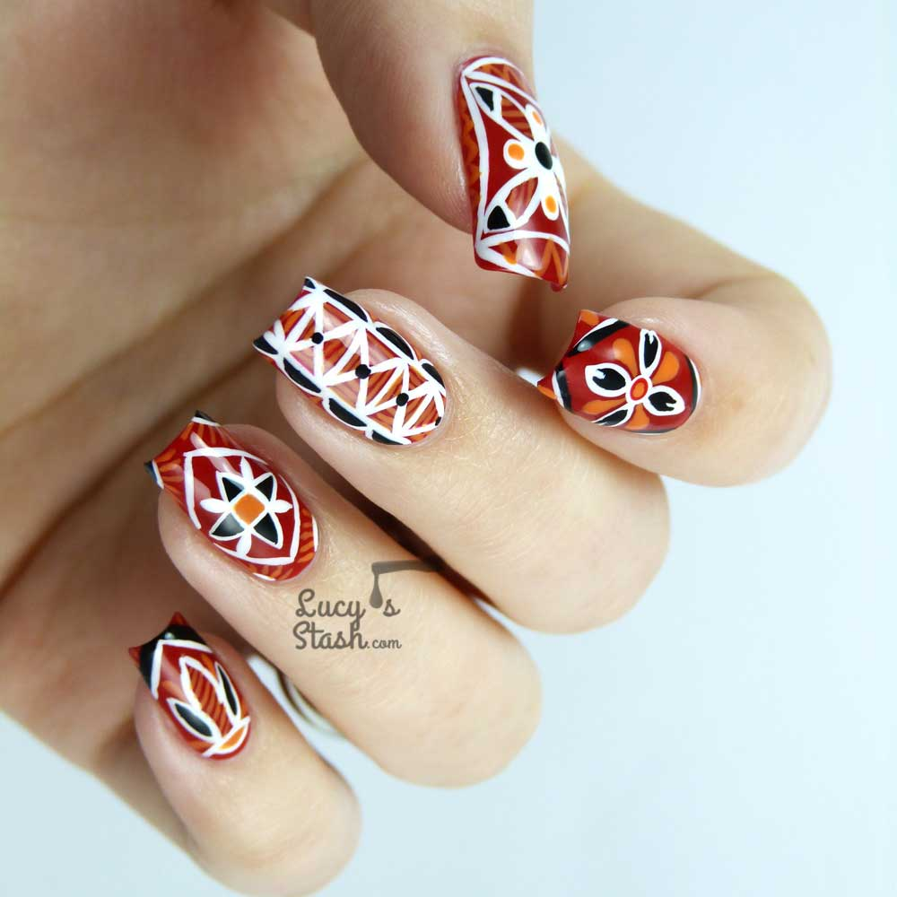 Painted fingernails with white and black patterns on red and orange backgrounds inspired by traditional Czech Easter egg painting