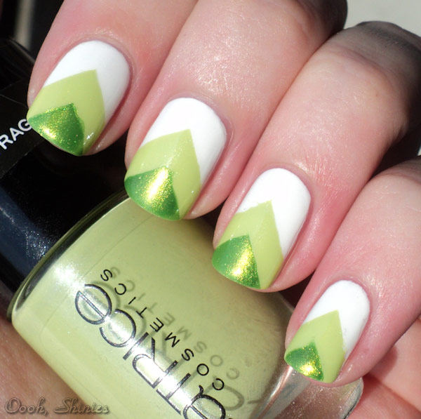 Fingernails with two-tone green triangle design on a white background.