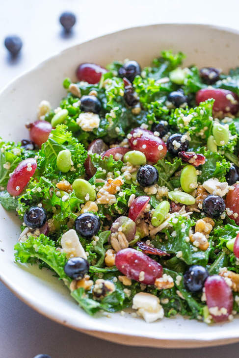 White bowl of mixed salad containing grapes, beans, lettuce, seeds and more.
