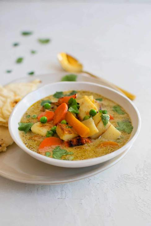 A white bowl of green curry with vegetables on a white tablecloth.