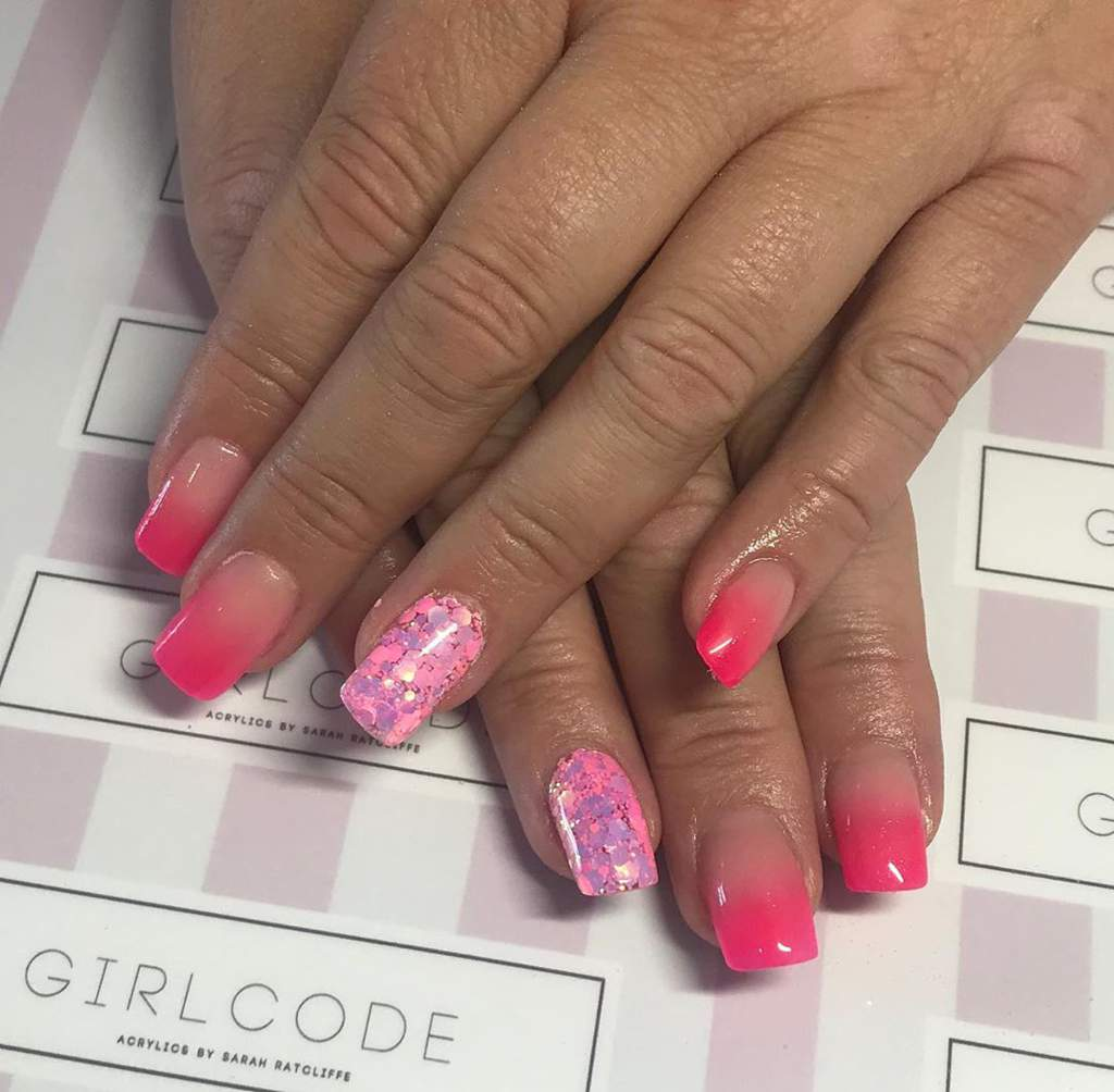 Hands with acrylic fingernails in pink ombre design and two with pink glitter design.