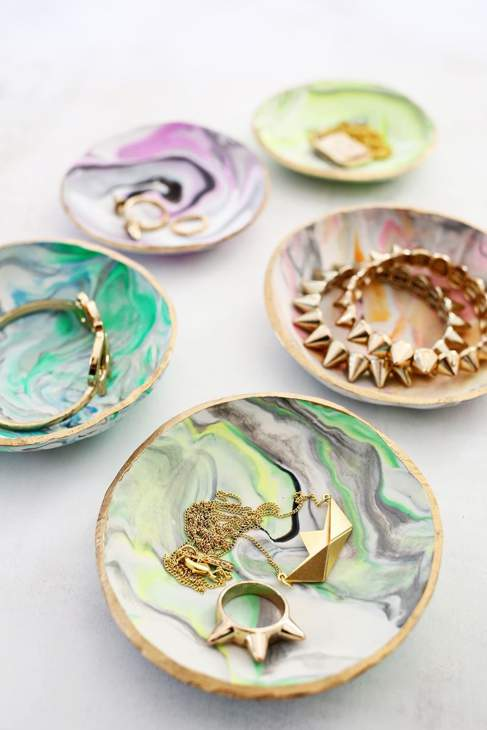 Five marble-effect ring dishes with jewellery inside.