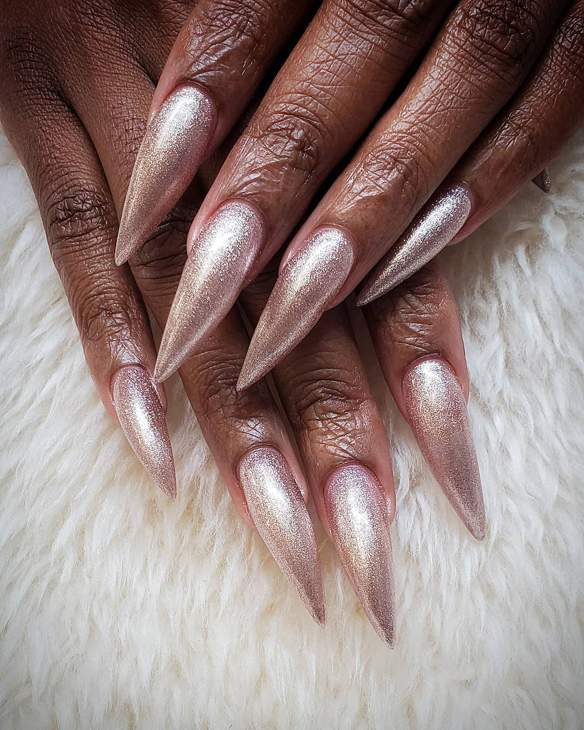 Two hands with dark skin and pink glittery nails on a background of white fur material.