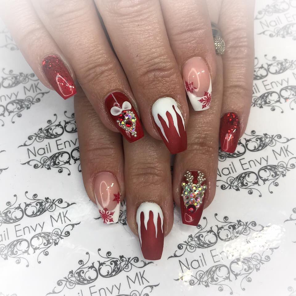Two hands with acrylic fingernails decorated in various Christmas designs in red and white including a flame pattern, jewelled reindeer, snowflakes, a jewelled bauble and red glitter.