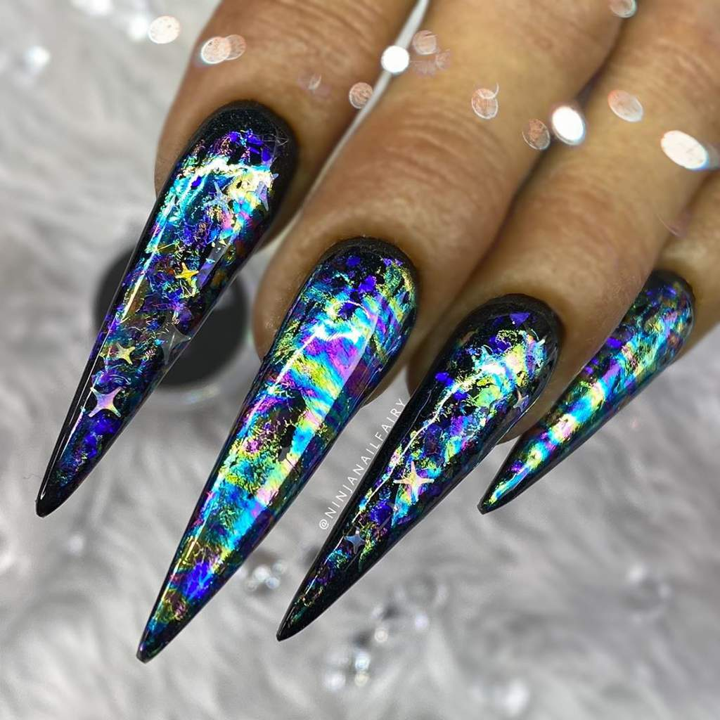 Hand with very long pointed acrylic fingernails in multi-colored oil-slick design.