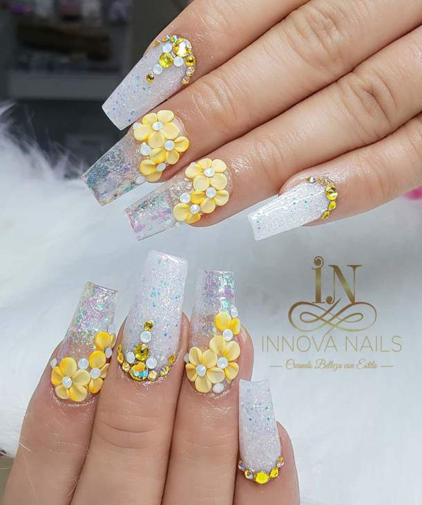 Two hands with clear frosted acrylic nails decorated with yellow flowers.