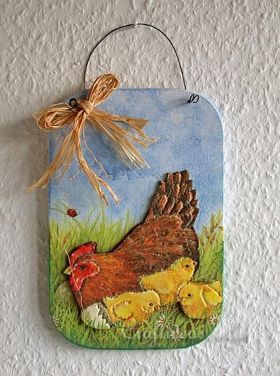 Painted wooden wall hanging decoration showing a brown hen with a red head and three yellow chicks in a grassy field under a blue sky. There is a string bow in the top left of the hanging.