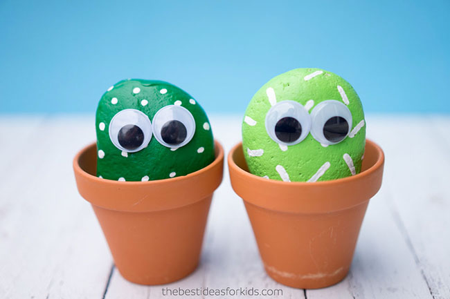 Two rocks painted green to look like cacti with stick-on eyes, sitting in earthenware pots
