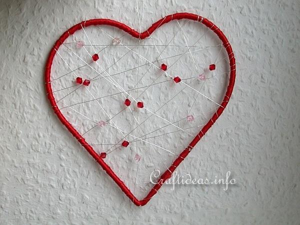 Red heart-shaped dreamcatcher with strings and red beads within the red frame,hanging on a white wall.